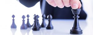 Picture of a man moving a chess piece - in the puzzle that is leadership